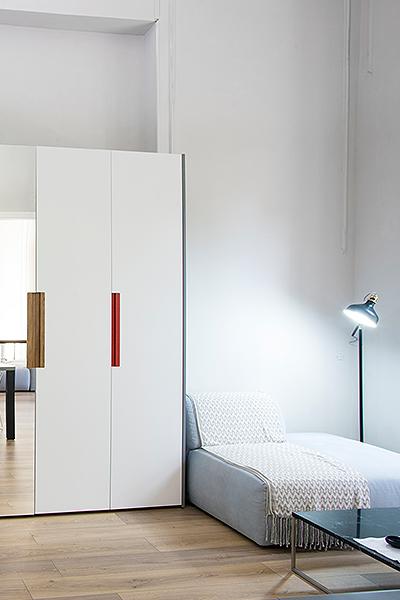 Kleiderschrank mit zwei weißen und einer Spiegeltür, grauen Seitenwänden, zwei Griffen in Eiche und einem in Rot